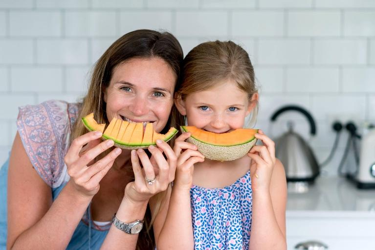 Mom and daughter eating fruit